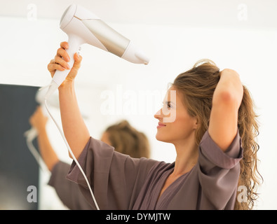 Young woman blow drying hair in bathroom - Stock Photo