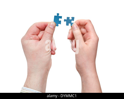 couple of male and female hands connecting little puzzle pieces isolated on white background
