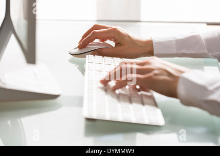 Woman using a mouse and keyboard Computer on desk - Stock Photo