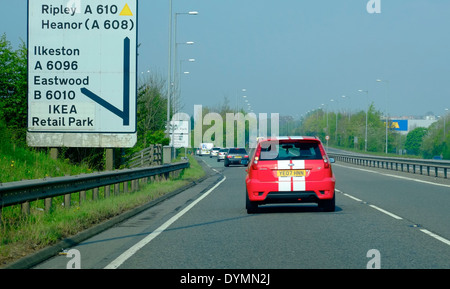 A red Ford Fiesta ST indicating to leave the dual carriageway exit near Ikea retail park Nottingham England uk - Stock Photo