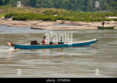 Horizontal view of 3 young Lao boys driving a long boat along the Mekong river. - Stock Photo