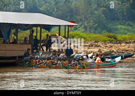 Horizontal view of brightly coloured power boats lined up waiting for passengers at a jetty along the Mekong river. - Stock Photo