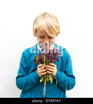 Blond boy with freckles wearing a blue top holding a bunch of purple sprouting broccoli - Stock Photo
