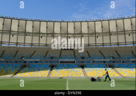 A groundsman prepares the pitch at Maracana stadium in Rio de Janeiro, Brazil, staging the soccer FIFA World Cup - Stock Photo