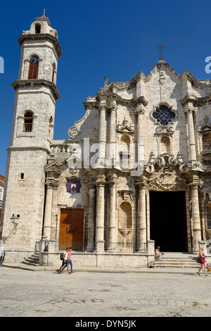 Tourists in Old Havana plaza in front of the Havana Cathedral with clock tower Cuba - Stock Photo