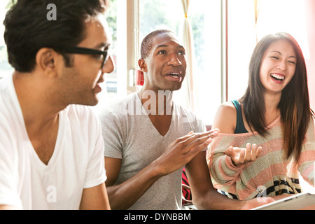 Friends laughing together in cafe - Stock Photo