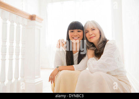 Mother and daughter hugging on steps - Stock Photo