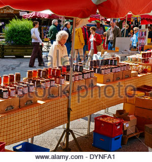 elderly grey haired woman looking at jams and preserves on an outdoor stall in a french open air street market - Stock Photo