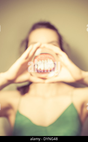 Young woman holding magnifying glass in front of mouth, showing her teeth. - Stock Photo