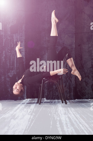 Woman performing acrobatic pose on chair - Stock Photo