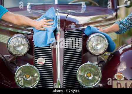 A male and female hand wiping down the front of historic Buick car in Pompano Beach, FL - Stock Photo