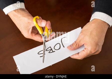 Closeup view of a business man cutting jobs. - Stock Photo