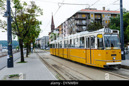Image Yellow tram on river bank of Danube. Yellow tram is part of transportation system in Budapest, Hungary - Stock Photo