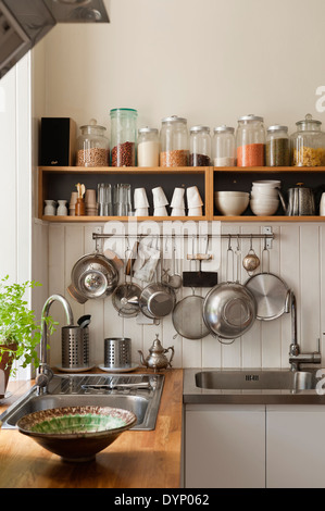 Dried ingredients on open shelving and utensils hanging from a pan rack in kitchen corner with sinks and solid oak - Stock Photo