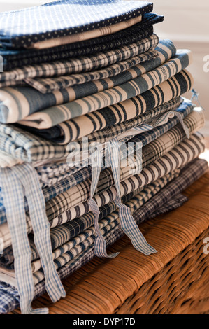A pile of assorted linens in blue and white stripes and checks folded on top of a wicker basket - Stock Photo