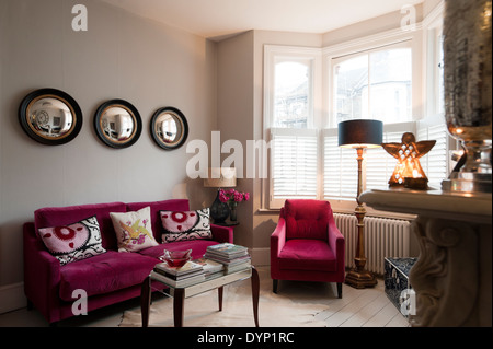 Raspberry coloured velvet furniture in living room with Graham and Green porthole wall mirrors - Stock Photo