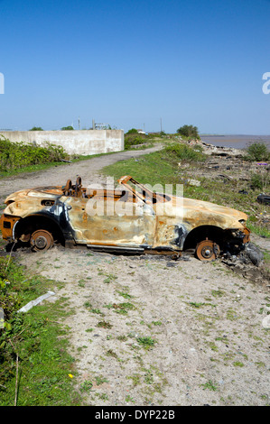 Burnt out car blocking Wales Coast Path, Rover Way, Cardiff, South Wales, UK. - Stock Photo