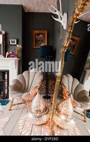 Marrakech Tyre Lamp by Graham and Green on floor of bedroom with scallop style armchair and dark painted walls - Stock Photo