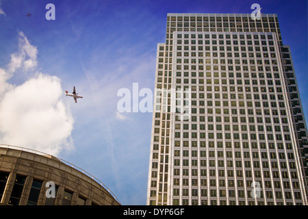 Two planes flying by the One Canada Square skyscraper in the new financial district of Canary Wharf, London, UK. - Stock Photo