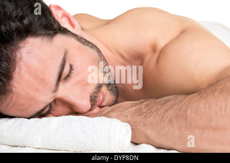 Man lying in a spa ready to get a massage, isolated in white - Stock Photo