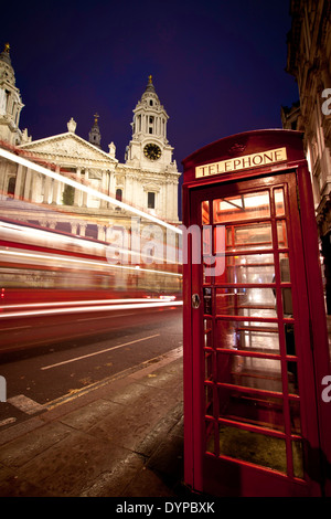 A red bus speeding past St Paul's cathedral, London, at dusk, with typical red phonebox in the foreground. Portrait - Stock Photo