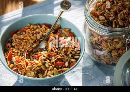 Serving of homemade granola on table with linens in morning sunlight - Stock Photo