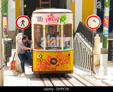 Passenger boarding the Elevador da Bica funicular for its steep ascent through district of Bica Lisbon Portugal - Stock Photo