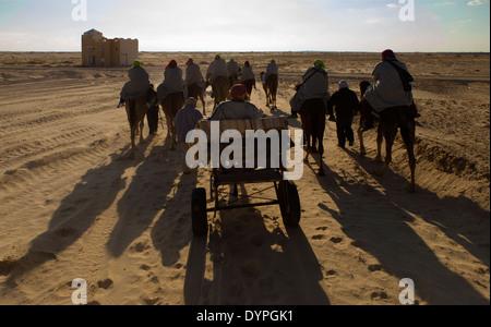 Camel ride in Sahara desert in Tunisia - Stock Photo