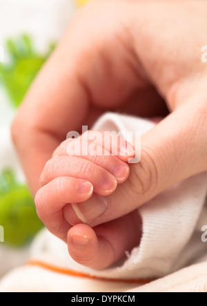 baby holding mother's finger - Stock Photo