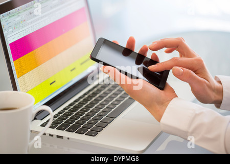 Businesswoman typing message on mobile phone in office. - Stock Photo