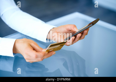 Woman shopping online using mobile phone and credit card .indoor.close-up - Stock Photo