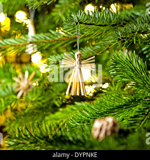 Straw Ornament in a real Christmas tree in bright color - Stock Photo