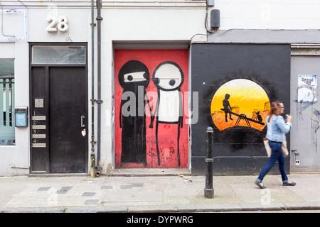 Stix holding hands on Princelet Street, London - Stock Photo