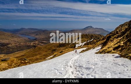 Walker descending snow on Ben Vane with views overlooking Loch Lomond and Ben Lomond, Scottish Highlands, UK - Stock Photo