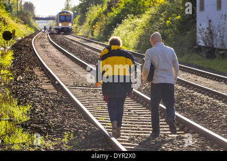 Lurgan, Northern Ireland. 24 Apr 2014 - Two forensic investigators walk along a railway track to the spot where - Stock Photo