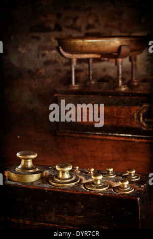 Antique brass weights with scales in the background. Distressed texture for a retro feel. - Stock Photo