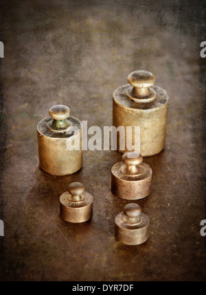 Vintage brass weights. Distressed texture for a retro feel. - Stock Photo