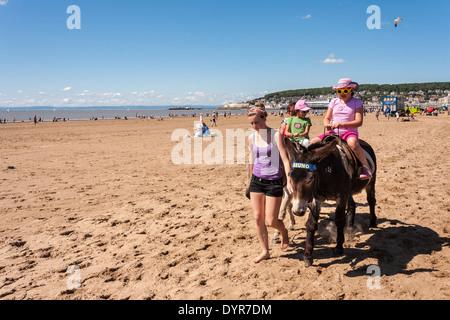 Children riding donkeys on the beach. Weston-Super-Mare, Somerset, England, GB, UK. - Stock Photo