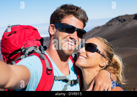 Happy couple taking photo of themselves with smart phone outdoors, Taking a 'selfie'