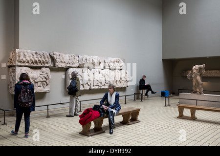 Tourists in room with Greek ancient marbles in British Museum, London - Stock Photo