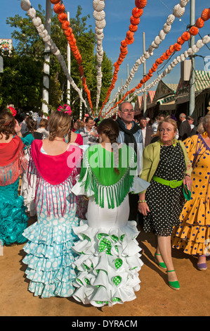 April Fair, Young women wearing a traditional flamenco dress, Seville, Region of Andalusia, Spain, Europe - Stock Photo