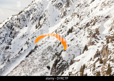 A tourist, tandem paraglides with a guide above the valley of Chamonix Mont-Blanc, taking off from Planpraz. - Stock Photo