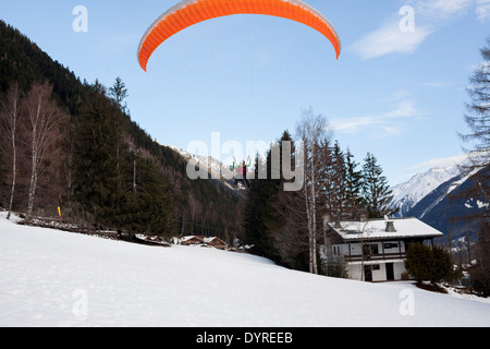 A tourist, approaches the landing while tandem paragliding with a guide in Chamonix Mont-Blanc. - Stock Photo