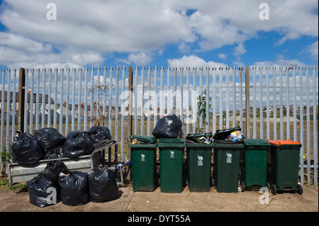 Domestic wheelie bins against industrial fence Newport South Wales UK - Stock Photo