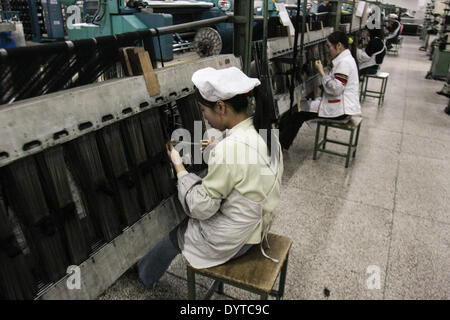 Workers operate a weaving machine at the Jiangsu Sunshine Co - Stock Photo