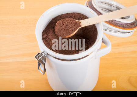 Fresh, ground coffee beans in a white ceramic canister on a wood table - Stock Photo