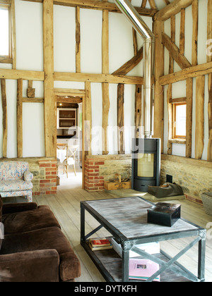 Living room in barn conversion with exposed beams, Field Place Barns, Surrey - Stock Photo