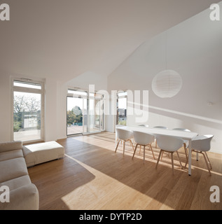 White table and chairs in modern open plan room, Maison Air et Lumiere, Verrieres-le-Buisson, France - Stock Photo