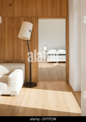 Floor lamp next to sofa with view through doorway to bedroom, Maison Air et Lumiere, Verrieres-le-Buisson, France - Stock Photo