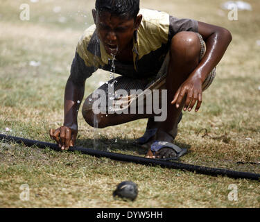 Dhaka, Bangladesh. 25th Apr, 2014. A boy drinking water from water pipe while playing on field.People in the capital - Stock Photo